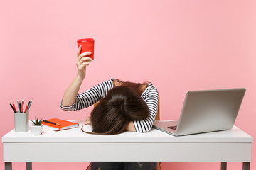 Exhausted woman laid her head down on the table holding cup of coffee or tea sit, work at white desk with pc laptop isolated on pastel pink background. Achievement business career concept. Copy space. Wall mural