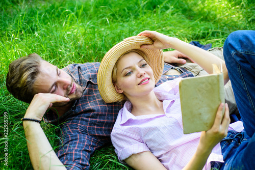 Man and girl lay on grass reading book  Family enjoy leisure