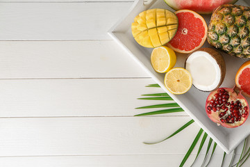 Tray with various delicious exotic fruits on light wooden table