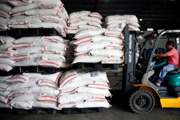 A volunteer operates a crate lifter to carry sacks of rice for victims of Super Typhoon Mangkhut at the Department of Social Welfare, National Relief Operations Center in Pasay City
