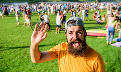 Man bearded hipster in front of crowd people green field background. Hipster in cap visiting social event picnic fest or festival. Urban event celebration. Man waving hand sunny day outdoors