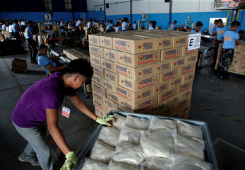 A volunteer pushes a cart of repacked rice for victims of Super Typhoon Mangkhut at the Department of Social Welfare and Development, National Relief Operations Center in Pasay City