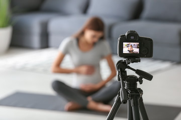 Young pregnant blogger recording video at home