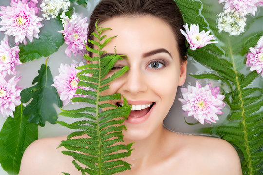 Portrait of young sexy beauty female woman smiling with clean pure skin taking spa relaxing in bath with flowers and green leafs white soap water. Skin beauty health care concept. Body part and nature