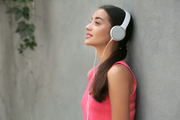 Beautiful young woman listening to music near grey wall outdoors