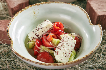 Vintage Stylized Fresh Vegetable Salad with Fragrant Herb Cheese on Rustic Hay Background