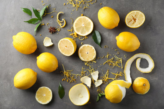 Composition with ripe lemons and fresh zest on grey background