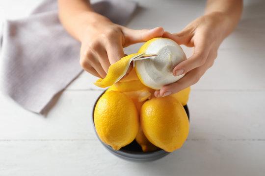 Woman peeling ripe lemons at white wooden table, closeup
