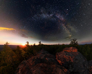 Dawn in the forest under the starry sky a milky way. Panorama.