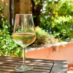 Autocollant pour porte Pique-nique A Glass of White Wine on a Table in the Garden