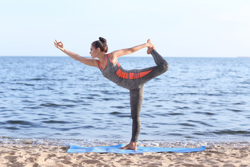 Woman practicing yoga on sea shore