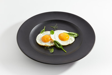 Fried Eggs Decorated with Fresh Spinach Leaves and Young Pea Shoots