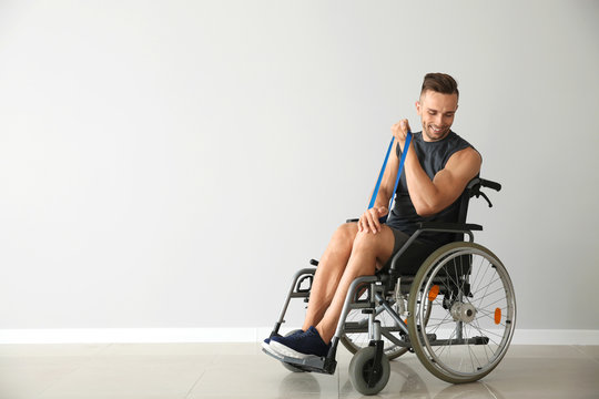 Sporty man training with elastic band while sitting in wheelchair against light wall