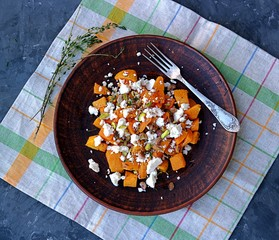 Autumn salad of roasted pumpkin with soft feta cheese, thyme and pistachios. Healthy food concept.