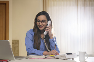 Smiling businesswoman on the telephone in the office