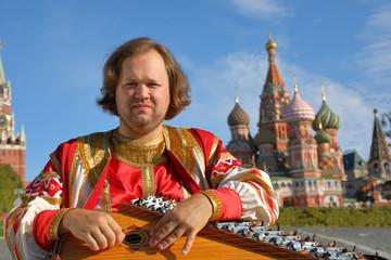 Minstrel playing an old Russian musical instrument gusli