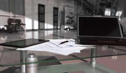 laptop and financial documents on a Desk in a spacious office