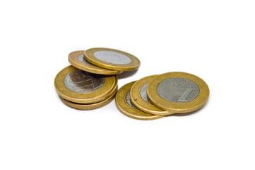 pile of Brazilian currency coins, in the present value of 1 one real, isolated on white background