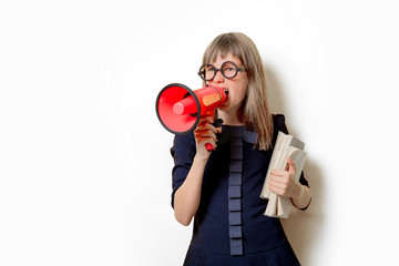 Portrait of a nerd girl in glasses with books and megaphone on white background