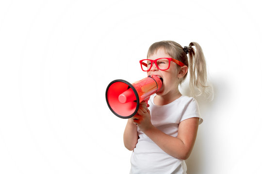 Portrait of an emotional toddler girl in glasses with megaphone on white background