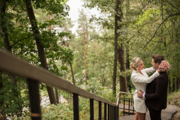 Embracing adult newlyweds in green woods