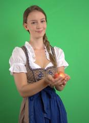 Junge Frau im Dirndl mit Apfel