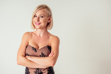 Blonde young woman in elegant lacy dress. Girl posing on a white background.