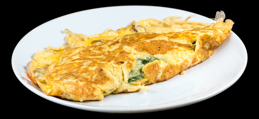 Omelet with organic spinach, cheese and mushrooms isolated on black background