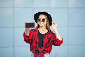 A woman in the street is smiling. A woman in black glasses with a smartphone. Selfy. Blue background