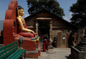 A woman offers prayer on the idol of Buddha at Swayambhunath Stupa, a UNESCO world heritage site in Kathmandu