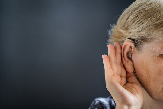 Elderly woman with hearing aid on black, grey background. Deafness concept.