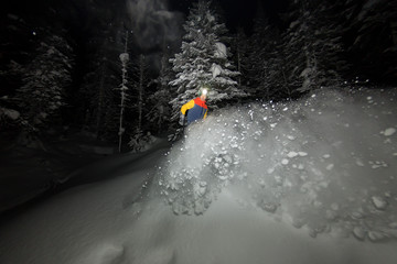 freerider snowboarder jumping at night with a springboard in the forest