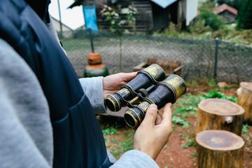 Old binoculars in hand