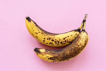 Overripe bananas on pink background, horizontal, top view