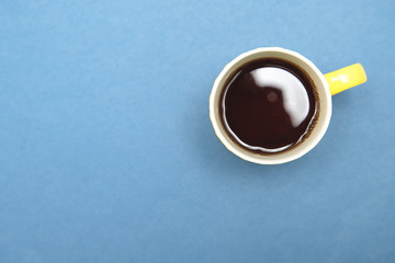 A yellow cup with tea on a blue background is a top view. Minimalism. Space for text. Background