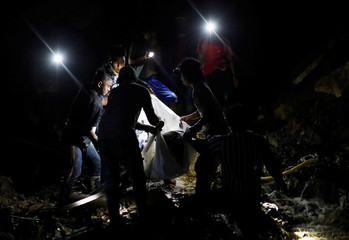 Rescuers carry the body of a fellow miner retrieved from the rubble of a bunkhouse after a landslide caused by Typhoon Mangkhut at a mining camp in Itogon