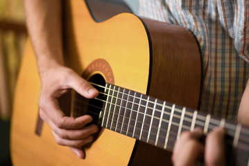 man playing classical acoustic guitar