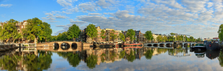 Printed roller blinds Amsterdam Beautiful panoramic panorama of the river Amstel and the skinny bridge (Magere brug) in Amsterdam, the Netherlands, on a sunny summer morning with some clouds and a mirror reflection