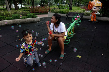 A mother blows soap bubbles as she spends time with her son at a park in Bangkok