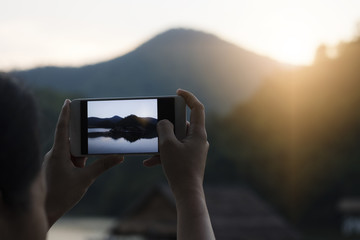Close up hand holding phone and take photo on landscape in sunset