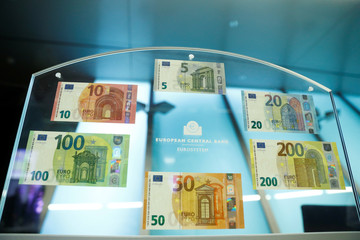 People hold new 100- and 200-euro banknotes during a presentation at the ECB headquarters in Frankfurt,