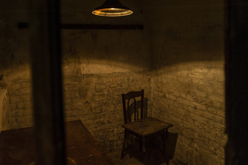 Prison guard room/Low light creepy penitentiary guardian observation room with a chair and a ceiling lamp.