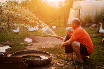 Grandfather and grandson playing with water hose in a backyard of a animal farm. Having fun on a summer day.