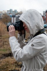 A girl in a white jacket takes pictures of nature near the lake