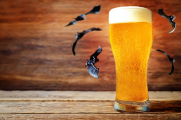 Glass of cold light beer with flying bats on a wood background for Halloween