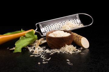 Fresh grated horseradish roots and grater.