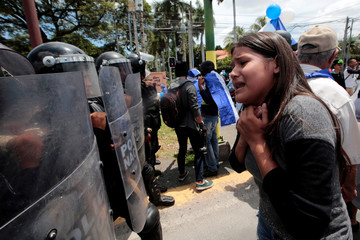 An anti-government protester shouts slogans in front of a line of riot police during a protest against Nicaraguan President Daniel Ortega's government in Managua