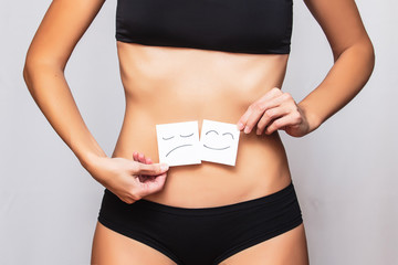Female body in black sports underwear close up with a smiley face on a piece of paper at the belly on an isolated background