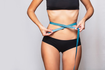 Female body in black sports lingerie close-up with measuring tape at waist on isolated background
