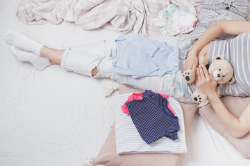 Pregnant woman with a teddy bear and various clothes for a newborn